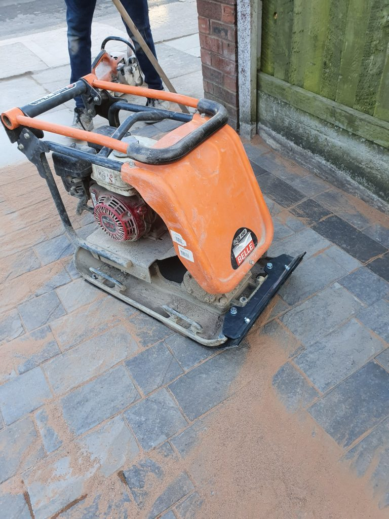 Belle plate compactor with rubber mat used to vibrate block paving into final position