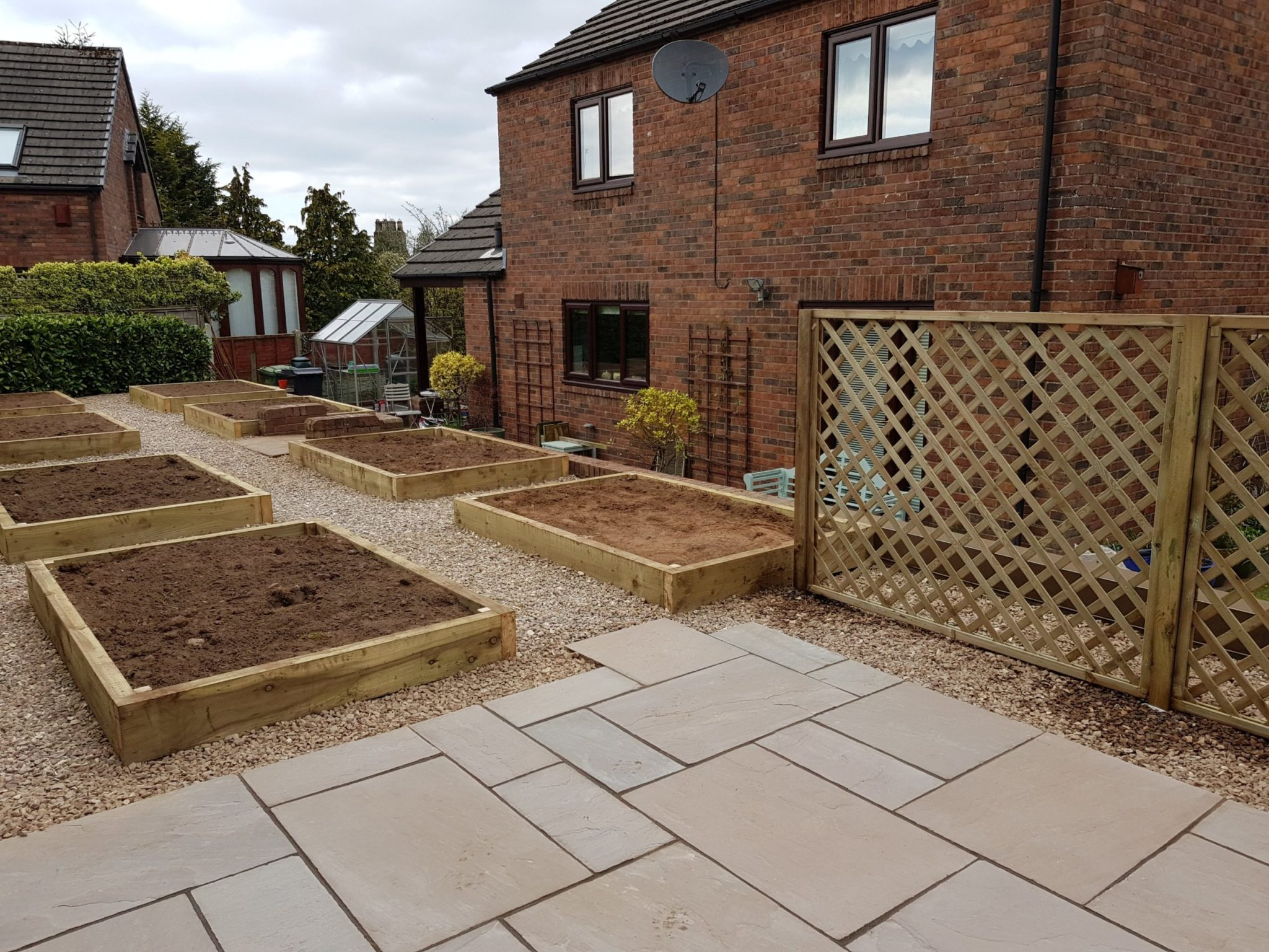 stone patio and wooden planters we landscaped in Brampton Cumbria