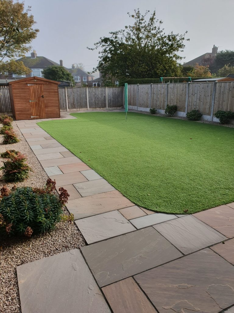 large artificial grass lawn with indian sandstone perimeter