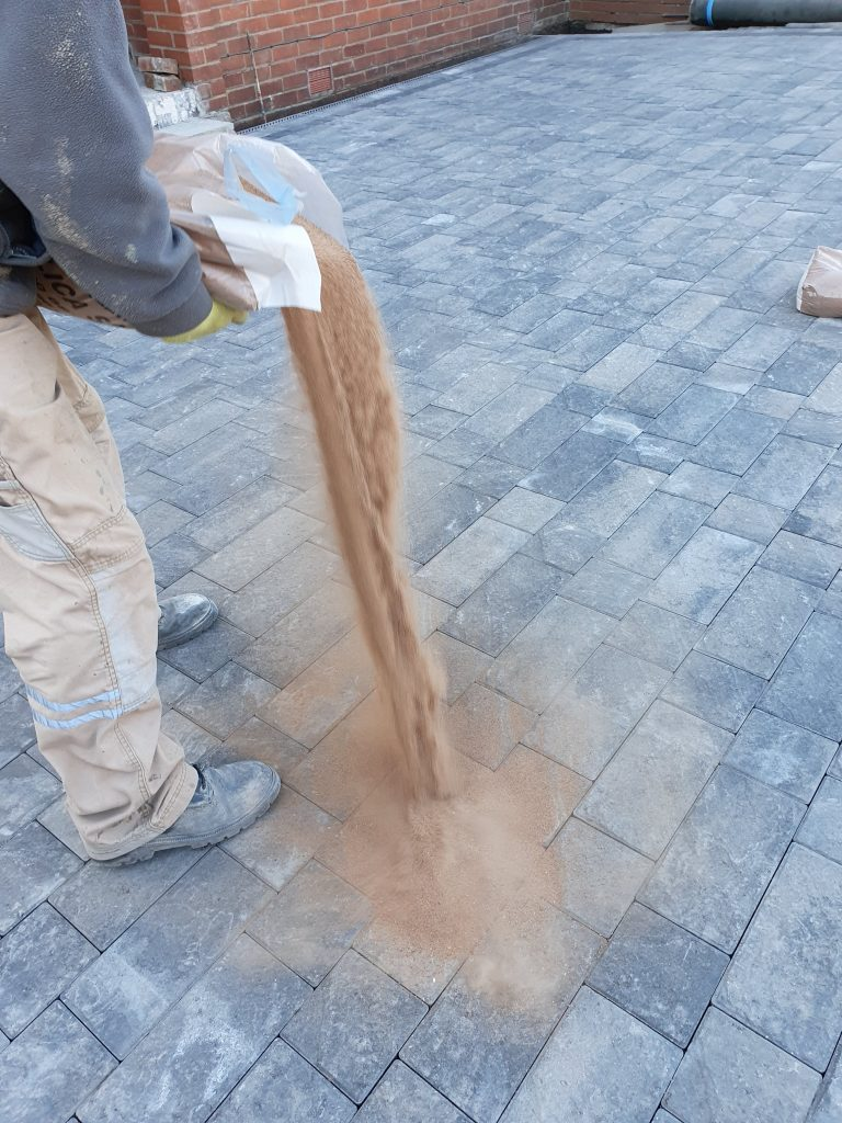 Silica sand poured on block paving to lock the blocks