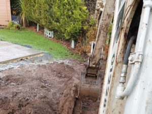excavtor in backyard with soil landscaping a Carlisle garden